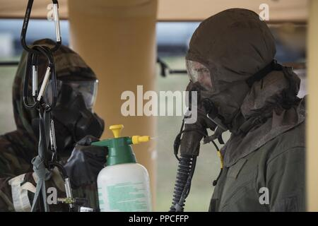 Senior Airman Austin Lebrun, left, 52nd Operation Support Squadron aircrew flight equipment journeyman, works on decontaminating Capt. Logan Mitchell, right, 52nd OSS AFE flight commander, during decontamination training at Spangdahlem Air Base, Germany, Aug. 23, 2018. This training was designed to simulate pilots landing in a potentially contaminated environment. - Stock Photo