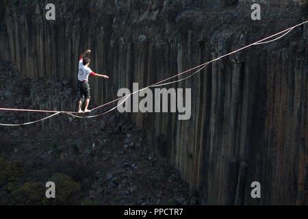 Man balancing on tightrope across Basaltic Prisms of Santa Maria Regla, Huasca de Ocampo, Hidalgo, Mexico - Stock Photo