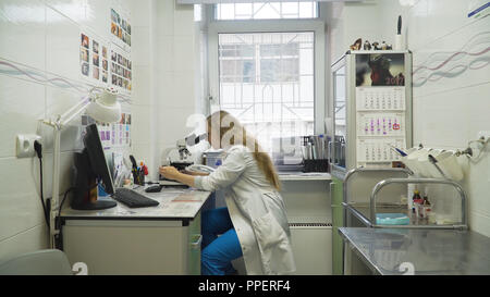 Doctor woman working with a microscope in Laboratory. Female scientist looking through a microscope in lab. Scientist using a microscope in a laboratory. - Stock Photo