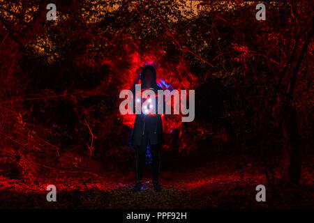 witch playing with lights like fire in the forest during halloween - Stock Photo