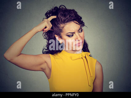 Young puzzled brunette woman in yellow dress scratching head in perplexion looking away - Stock Photo