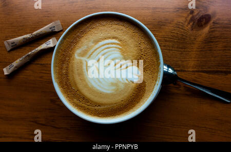 An extra large cappuccino in a bowl with a milk foam leaf, two sugars on the side and a spoon - Stock Photo