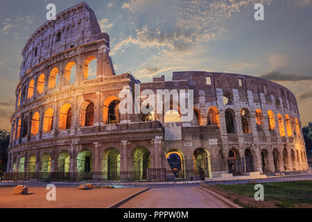 Roman Coliseum enlighted in the evening under the clouds - Stock Photo