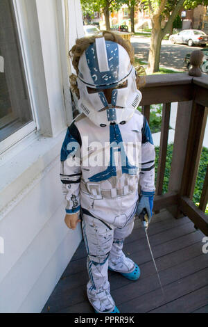 Young boy on his front porch defending his home in a Star Wars Clone Trooper costume holding a light saber. Chicago Illinois IL USA - Stock Photo