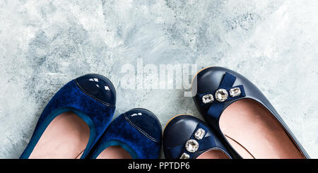Several Pairs of Female Flat Shoes, Ballerinas on grey background - Stock Photo