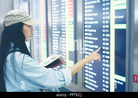 beautiful travel woman using smartphone at airport. Young asian traveler checking boarding time with mobile phone app in terminal or train station. To - Stock Photo