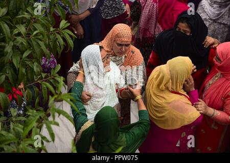 Pulwama, Kashmir, India. 27th Sep, 2018. Kashmiri women comfort the relative of slain rebel, Irfan Ahmad, who was killed at Chadoora encounter in Budgam district of Indian-Administered-Kashmir on Thurday, September 27, 2018. Irfan Ahmad was killed in an encounter between rebels and Indian forces at Panzan Chadoora in Budgam district. Three rebels, two civilians and a police personnel were killed in two seperate gunfights and a search operation in Kashmir on Thursday. (Credit Image: © Sanna Irshad MattooZUMA Wire) - Stock Photo
