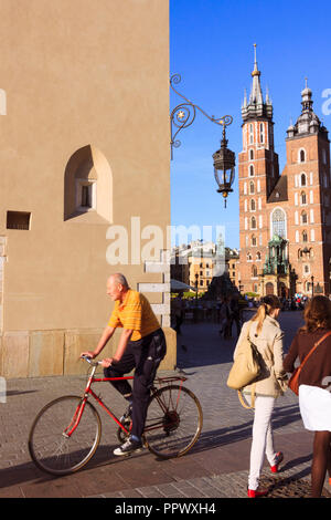 Krakow, Poland : A man cycles past the Cloth Hall and St. Mary's Basilica Church at the Main Market Square in Krakow Old Town. - Stock Photo