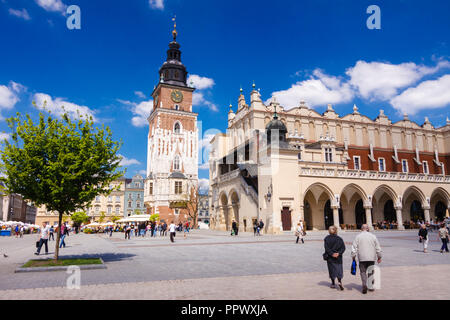 Krakow, Poland : People walks towards the Cloth hall building and old Town Hall Tower at the center of the main market square in the Krakow Old Town ( - Stock Photo