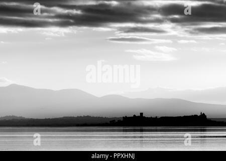 Beautiful view of Trasimeno lake at sunset Castiglione del Lago town in the background - Stock Photo