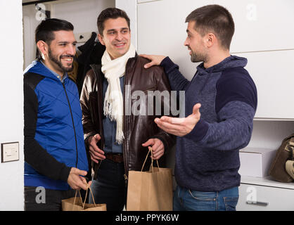 Two smiling men coming to visit their friend at home - Stock Photo