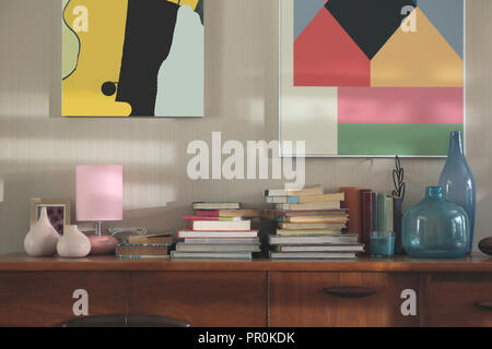 book stack put on a sideboard desk in retro style living room - Stock Photo