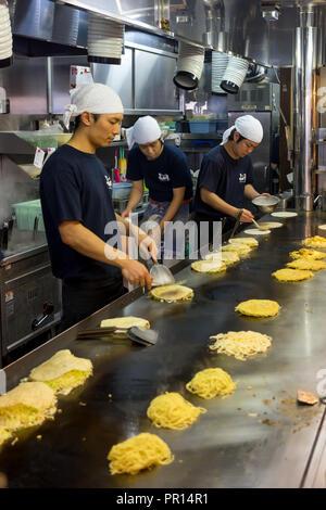 Okonomiyaki being prepared in a restaurant in Hiroshima, Japan, Asia - Stock Photo