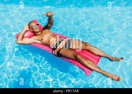 african american man showing thumb up while sunbathing on inflatable mattress in swimming pool - Stock Photo