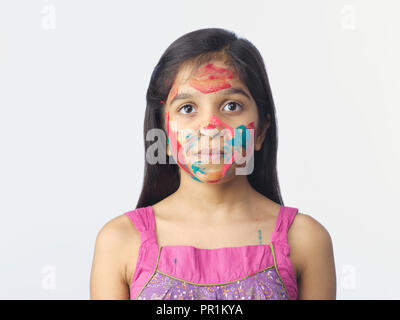 YOUNG GIRL WITH COLOURS ON HER FACE AND HANDS AFTER PLAYING THE FESTIVAL OF HOLI IN INDIA. SHOT AGAINST A PLAIN BACKGROUND - Stock Photo