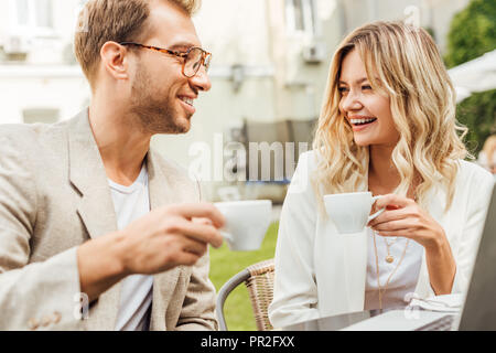 laughing couple in autumn outfit sitting at table with laptop and drinking coffee in cafe - Stock Photo