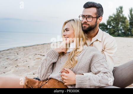 cheerful couple in autumn outfit sitting and hugging on beach - Stock Photo