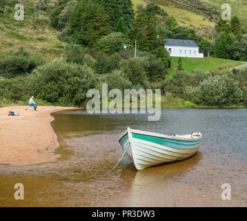 A lone fisherman and a boat on the beach at Lough Nafooey in the Connemara region of County Galway in Ireland. - Stock Photo