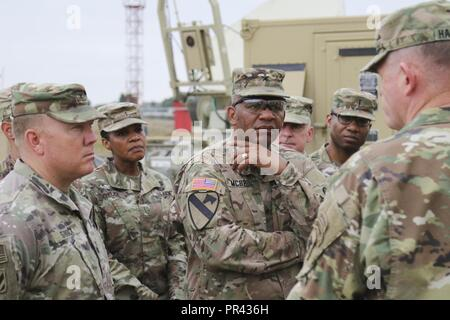 Brig. Gen. Douglas McBride, center, commanding general of the 13th Expeditionary Sustainment Command, listens as Maj. Gen. Joseph P. Harrington, far right, U.S. Army Africa commander, speaks with Soldiers from the 35th Signal Brigade on July 29, 2017, about the job they are doing during Exercise Judicious Activation 17-2 in Libreville, Gabon. Judicious Activation is a U.S. Africa Command exercise, executed by U.S. Army Africa this cycle, focused on increasing contingency response force capacity to support stability operations on the African continent. ( - Stock Photo