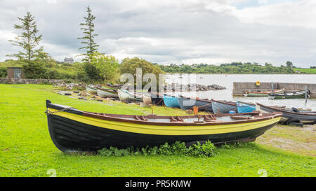 Colourful rowing boats lined up at Annaghdown Pier in County Galway in Ireland. - Stock Photo