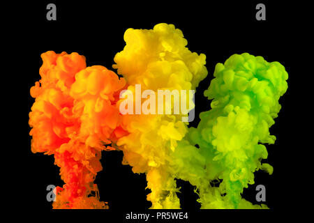 Orange, yellow and green paint in water, isolated on a black background. - Stock Photo