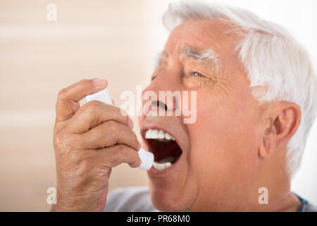 Close-up Of A Senior Man Using Asthma Inhaler - Stock Photo