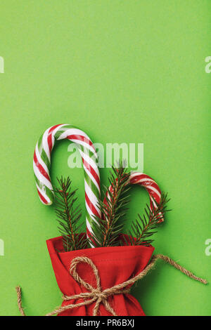 Bag of red color with Christmas gifts on green background with copy space - Stock Photo