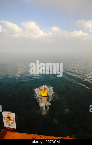 Young Man Jumping Into The Sea Young Man Jumping Into The Sea - Stock Photo