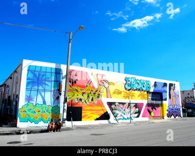 Girls having popsicle & sitting on streets of Wynwood, Miami. - Stock Photo