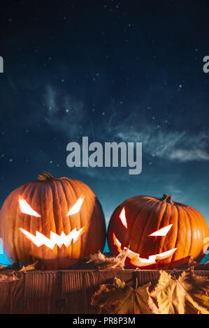 Two halloween pumpkins on fence with starry sky in the background. Vertical orientation - Stock Photo