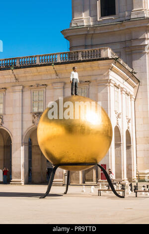 "Salzburg, Austria - May 29, 2017: The sculpture ""Sphaera"" by Stephan Balkenhol on Kapitelplatz. Famous sculpture of a man standing on a golden globe. - Stock Photo"
