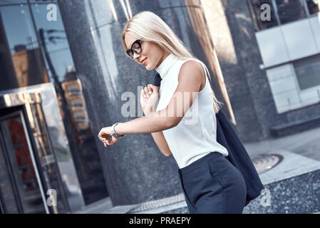 Business woman blond in glasses hurrying to a meeting. She smiles - Stock Photo