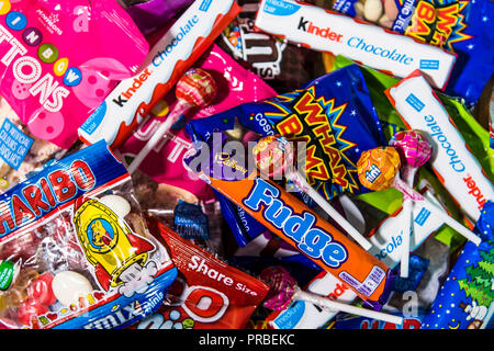 Assorted candy chocolate bars and sweets in brightly coloured wrappers. - Stock Photo