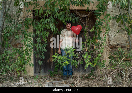 a scary disfigured man, wearing dirty and ragged clothes, with a red heart-shaped balloon in front of the door of an abandoned house covered by weeds - Stock Photo