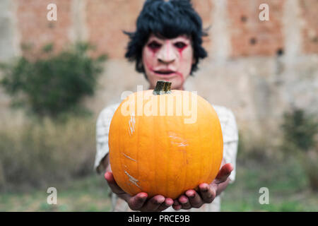 closeup of a scary disfigured man, wearing ragged and dirty clothes with blood stains, holding a pumpkin in his hands, in front of an abandoned house - Stock Photo