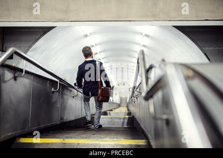 Rear view of hipster businessman walking down the stairs in subway, travelling to work. - Stock Photo