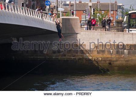 Boys hanging from the Samuel Beckett Bridge above the River Liffey, North Dock, Dublin, Leinster, Ireland - Stock Photo