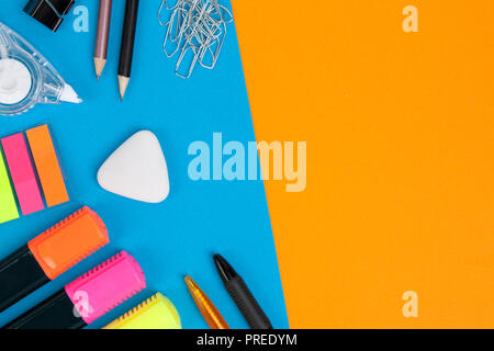 Two pens, two pencils, many paperclips, one eraser, three markers, one correction tape and one clip lie on blue background. Orange background with cop - Stock Photo