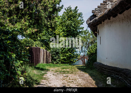 Traditional thatched roof building and lush green garden by the Lake Balaton, on Tihany peninsula, Hungary, Eastern Europe - Stock Photo