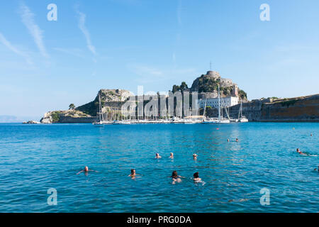 People swimming in the sea near to the Old Venetian Fort in Corfu Town, Corfu, Greece - Stock Photo