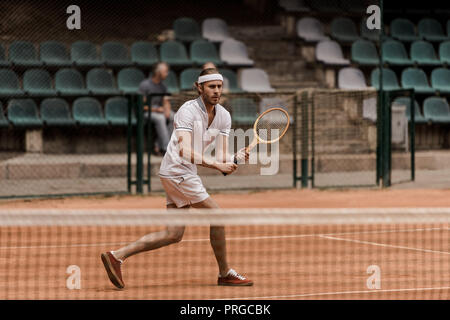 concentrated retro styled man playing tennis at court - Stock Photo