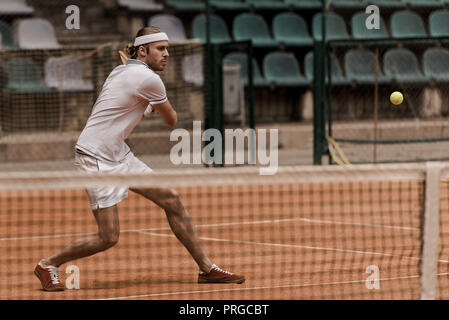 focused handsome retro styled man playing tennis at court - Stock Photo