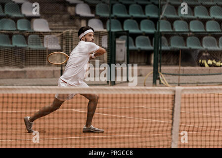 concentrated handsome retro styled man playing tennis at court - Stock Photo