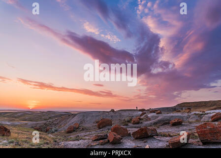 A particularly colourful sunset at the Red Rock Coulee Natural Area in southeast Alberta, with a lone figure silhouetted against the sky.  This is a 7 - Stock Photo