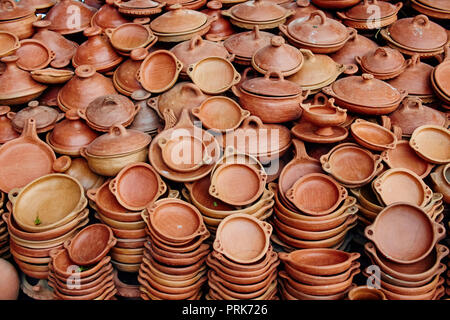 Large number of pottery sold in the streets of Morocco. Clay plates national dishes tajine. Making pottery by hand artisans - Stock Photo
