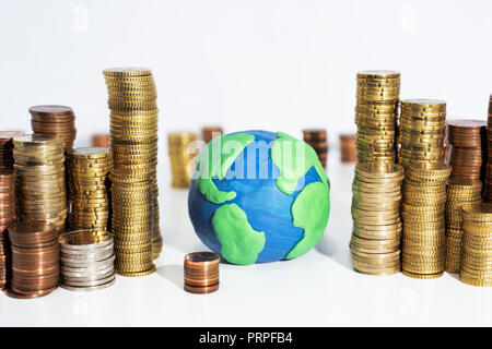 A lot of coins on white table with Earth model. Abstract photo of money. - Stock Photo