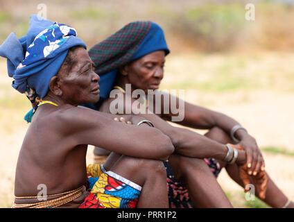 Mucubal tribe women sit, Namibe Province, Virei, Angola - Stock Photo