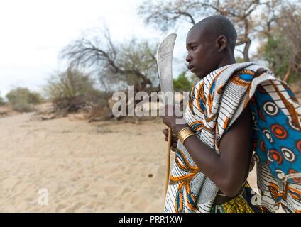 Mucubal tribe man with his machete, Namibe Province, Virei, Angola - Stock Photo