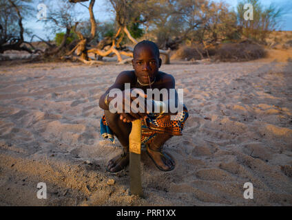 Mucubal tribe man with his machete sit in a dry river, Namibe Province, Virei, Angola - Stock Photo