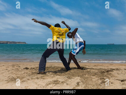Angolan boys dancing capoeira on the beach, Namibe Province, Namibe, Angola - Stock Photo